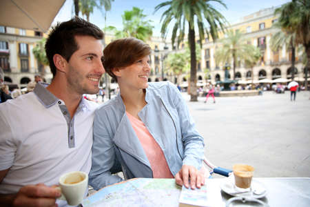 Couple in Barcelona sitting at restaurant table in Plaza Real photo