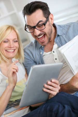 Couple reading news on both internet and paper Stock Photo - 19753963