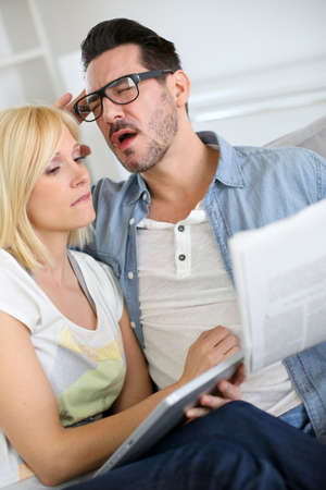 Couple reading news with horrified look photo
