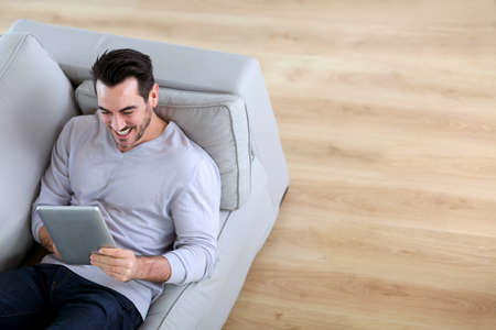 Upper view of man using tablet sofa photo