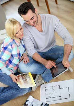 house renovation: Couple looking at new home construction plan
