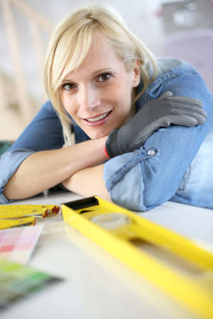 doityourself: Closeup of blond woman using level Stock Photo