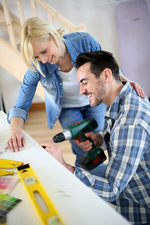 Couple installing furniture in new house photo