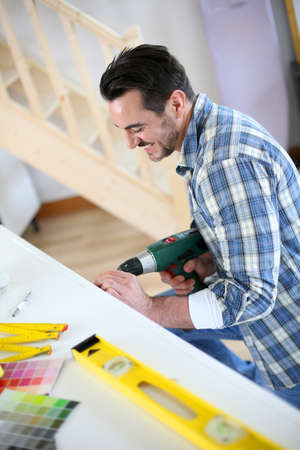 Man using electric drill in new house photo