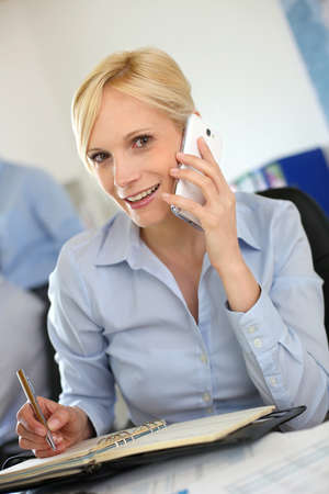 phonecall: Businesswoman on the phone writing on agenda