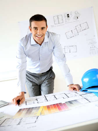 drawing table: Smiling architect leaning on desk in office Stock Photo