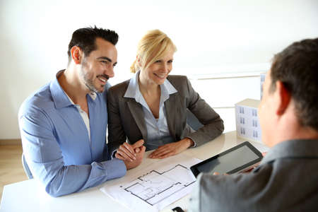 bankers: Couple meeting real-estate agent to buy property Stock Photo