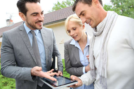 Real-estate-agent showing house plan on digital tablet Stock Photo - 19753968