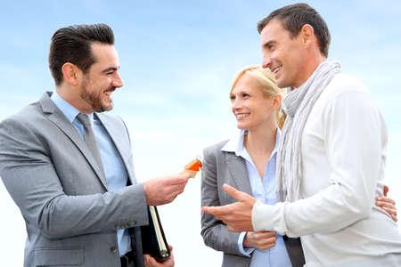 vendedores: Salesman dar llaves de la casa a los propietarios Foto de archivo