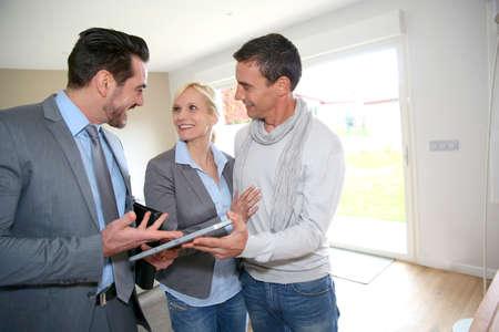 Paar mittleren Alters besucht Haus mit Verk?ufer Standard-Bild