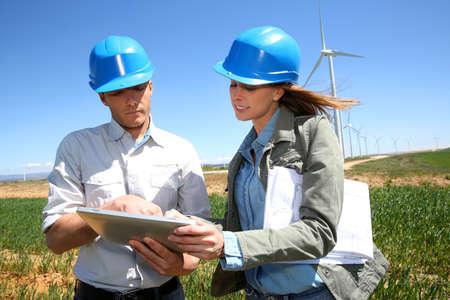 Engineers using tablet on wind turbine site photo