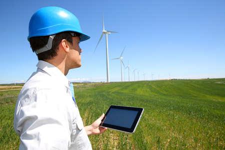 windturbine: Businessman checking on wind turbine energy production Stock Photo