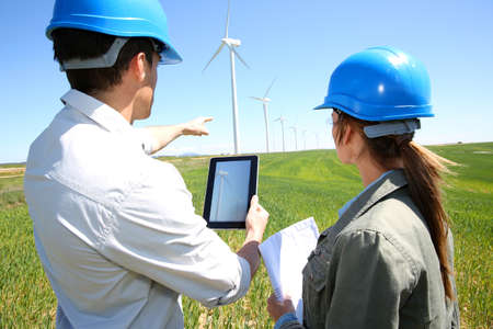 Engineers using tablet on wind turbine site photo