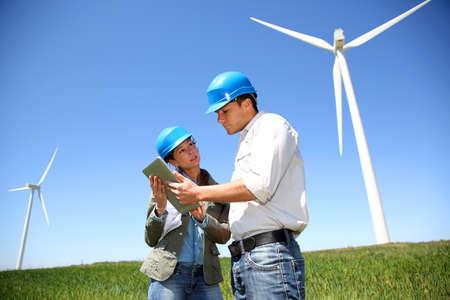 wind turbines: Engineers looking at wind turbine site with tablet