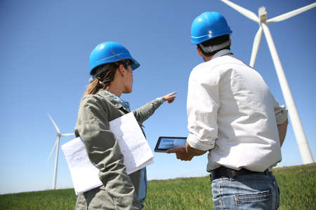 power in nature turbine: Engineers looking at wind turbine site with tablet