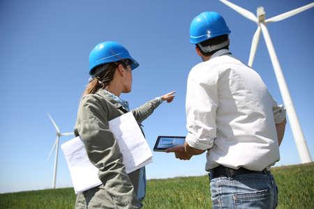 turbina: Ingenieros buscando en el sitio de la turbina de viento con la tableta