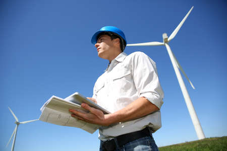 Engineer in wheat field checking on turbine production photo