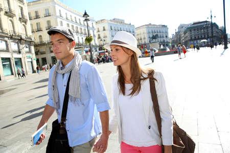 Couple walking by la Puerta del Sol, Madrid photo
