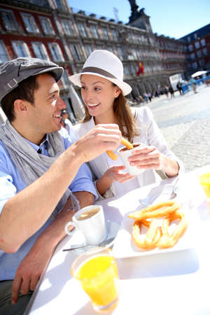Cheerful couple of tourists eating churros in Madrid photo