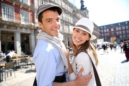 people smiling: Couple of tourists visiting la Plaza Mayor de Madrid Stock Photo