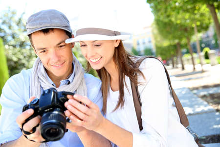 Cheerful couple with photo camera in touristic area photo