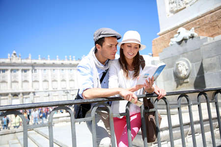 real madrid: Couple reading traveler book by the Royal Palace of Madrid