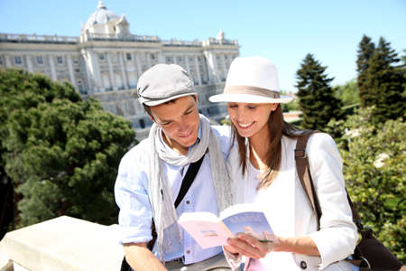 Couple reading traveler book by the Royal Palace of Madrid photo