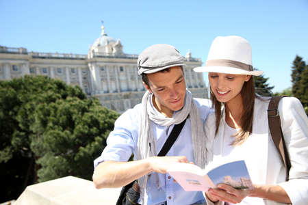 visitors: Couple reading traveler book by the Royal Palace of Madrid