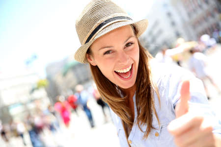 Portrait of cheerful girl in town showing thumbs up photo