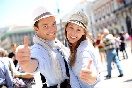 Cheerful couple in Madrid showing thumbs up photo