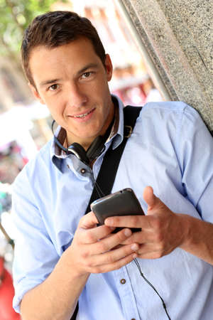 caucasian man: Man checking mails on smartphone in city street Stock Photo