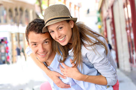 Man giving piggyback ride to girlfriend in town photo