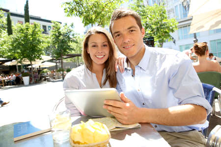 visitors: Couple connected on digital tablet in Santa Ana square Stock Photo