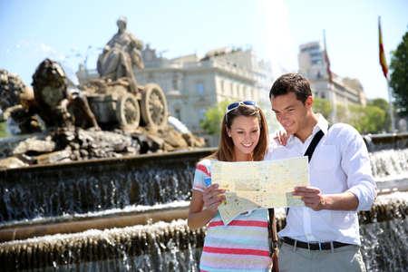 Couple of tourists reading map in Plaza de Cibeles, Madrid photo