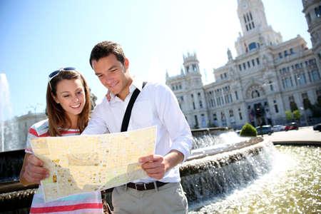 palacio de comunicaciones: Couple of tourists reading map in Plaza de Cibeles, Madrid