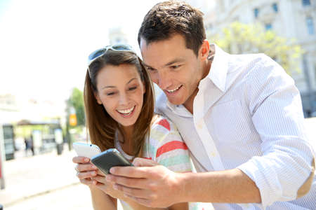 mobile: Couple of tourists in Madrid using smartphone