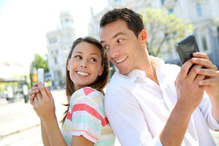 palacio de comunicaciones: Couple of tourists in Madrid using smartphone