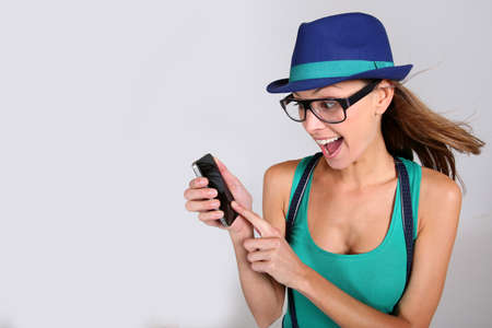 attitude girls: Funny girl with hat and eyeglasses showing smartphone