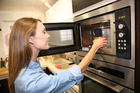 microwave: Woman heating dish in microwave