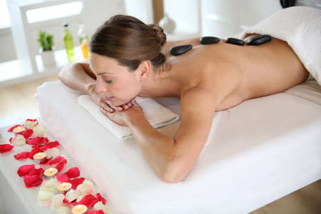 wellness center: Attractive woman enjoying hot stones massage Stock Photo