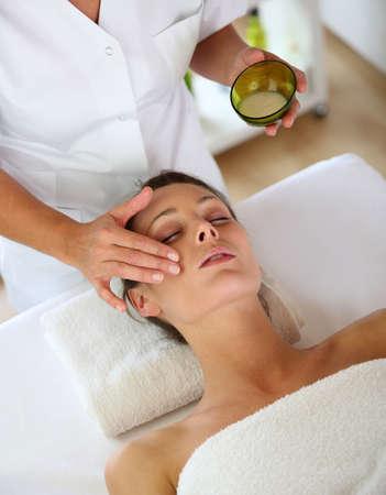 tratamiento facial: Una mujer recibe un masaje facial