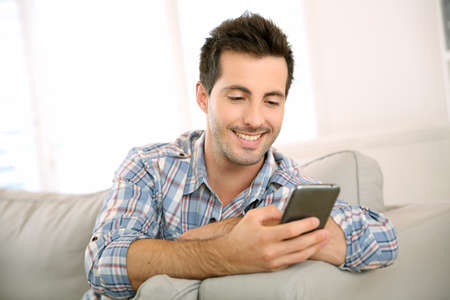 happy man: Handsome man using smartphone at home