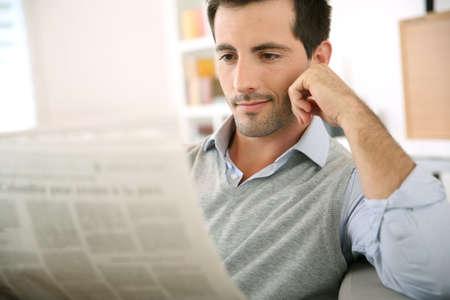 L'uomo a leggere il giornale a casa Archivio Fotografico - 20168676