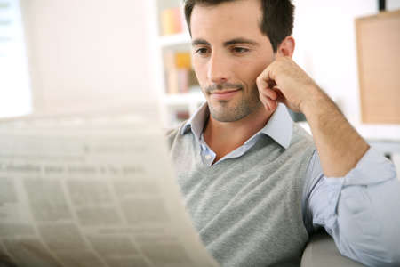 reading: Man at home reading newspaper Stock Photo