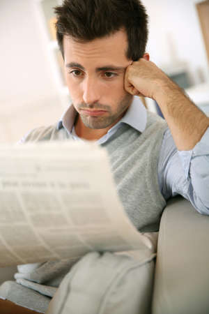 Man sitting in sofa and reading bad news photo