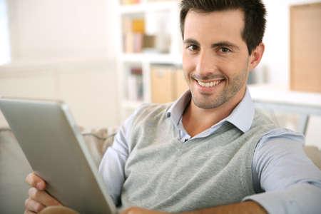 websurfing: Smiling man websurfing on internet with tablet