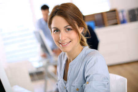 Portrait of cheerful girl in office photo
