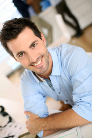 Portrait of cheerful man sitting in office photo