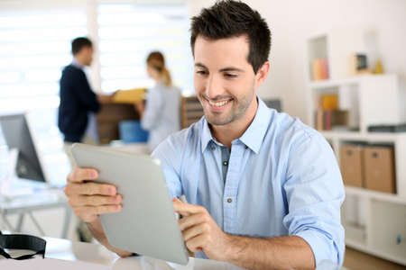 Smiling man in office working on digital tablet photo