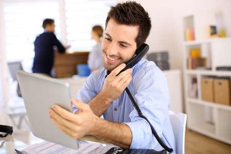 Vrolijke man in het kantoor van het beantwoorden van de telefoon